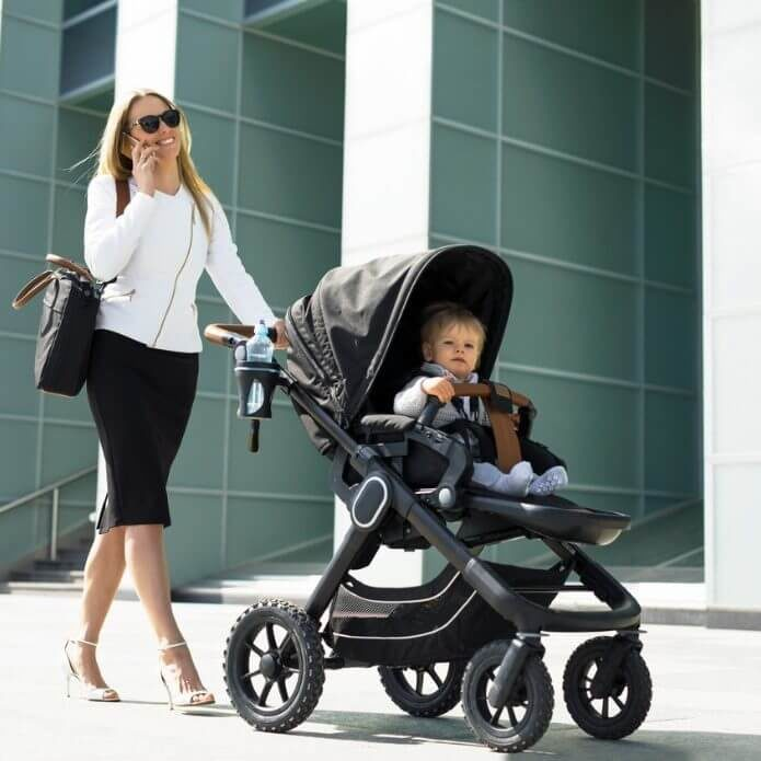 business-woman-with-baby-carriage-walking-and-talking-on-the-phone-picture-id852047318-square