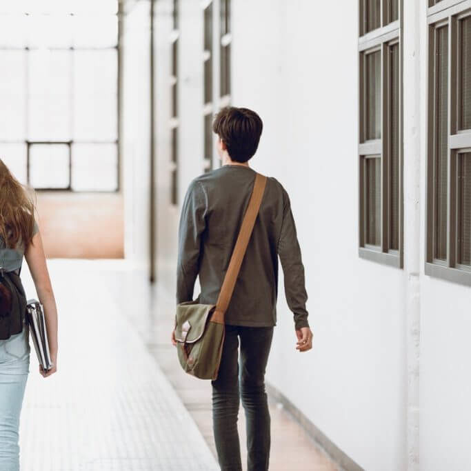 two-teenagers-walking-in-the-corridor-at-school-rear-view-one-boy-and-picture-id937049066-square
